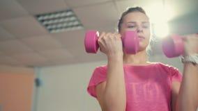 Το φίλαθλο κορίτσι κάνει την άσκηση με τους αλτήρες επάνω στην κατάρτιση στη γυμναστική απόθεμα βίντεο