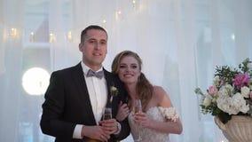 Το φίλημα νυφών και νεόνυμφων στο γαμήλιο συμπόσιο Νέο αγαπώντας γαμήλιο ζεύγος στη σκηνή απόθεμα βίντεο