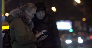 Το φίλοι γυναικών που χρησιμοποιούν το PC ταμπλετών κατά αναμονή το λεωφορείο στην οδό απόθεμα βίντεο