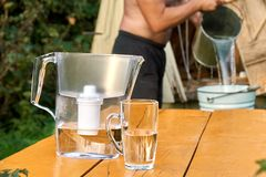 Το φίλτρο νερού με ένα φλυτζάνι με έναν γυμνόστηθο λιγότερη έκχυση ατόμων ποτίζει από ένα φρεάτιο στοκ εικόνα με δικαίωμα ελεύθερης χρήσης