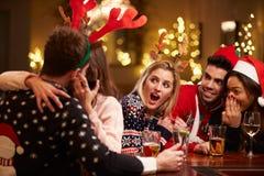 Το φίλημα ζεύγους στο φραγμό ως φίλους απολαμβάνει τα ποτά Χριστουγέννων Στοκ φωτογραφία με δικαίωμα ελεύθερης χρήσης