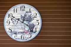 Το φανταχτερό ρολόι πεταλούδων και λουλουδιών διακοσμεί στον ξύλινο τοίχο Στοκ Φωτογραφίες