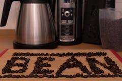 Το φασόλι λέξης που καταγράφεται σε ένα ελαφρύ ξύλινο υπόβαθρο που διαμορφώνεται στοκ φωτογραφία