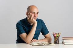 Το φαλακρό άτομο κάθεται στο γραφείο και τη σκέψη Στοκ φωτογραφία με δικαίωμα ελεύθερης χρήσης