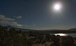 Το φεγγάρι απεικονίζει από τη λίμνη Abiquiu κάτω από το νυχτερινό ουρανό στοκ εικόνα με δικαίωμα ελεύθερης χρήσης
