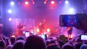 Το φεστιβάλ βράχου, πολλοί άνθρωποι με τη συσκευή στα χέρια κάνει την τηλεοπτική καταγραφή στη συναυλία απόθεμα βίντεο
