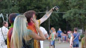 Το φεστιβάλ χρωμάτων Holi, άνθρωποι ομάδας στη φωτεινή σκόνη κάνει το selfi σε αρρενωπό σε υπαίθριο, η νεολαία με την τρίχα χρώμα απόθεμα βίντεο