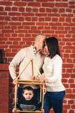 Το φιλί πατέρων και μητέρων, και γιος κρυφοκοιτάζει από ένα αυτοσχεδιασμένο σπίτι στο στούντιο στο υπόβαθρο του τουβλότοιχος διάσ στοκ εικόνα με δικαίωμα ελεύθερης χρήσης