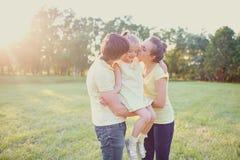 Το φιλί Arents και αγκαλιάζει την κόρη τους στο πάρκο Στοκ Εικόνες