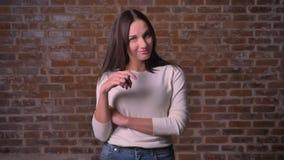 Το φλερτ γυναικών με τη κάμερα και το στρίψιμο της τρίχας της στο δάχτυλο στο α το υπόβαθρο φιλμ μικρού μήκους