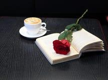 Το φλιτζάνι του καφέ, ένα κόκκινο αυξήθηκε και ένα βιβλίο στον πίνακα Στοκ εικόνες με δικαίωμα ελεύθερης χρήσης