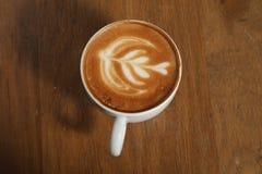 Το φλιτζάνι του καφέ συμπαθητικό σύρει στην κρέμα στοκ φωτογραφία