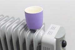 Το φλυτζάνι βάζει στη θερμάστρα πετρελαίου για τη θέρμανση στοκ εικόνες με δικαίωμα ελεύθερης χρήσης