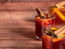 Το φλυτζάνι γυαλιού του κόκκινου κρασιού θέρμανε το κρασί σε ένα ξύλινο υπόβαθρο με τα καρυκεύματα και το πορτοκάλι κανέλας Εκλεκ Στοκ φωτογραφίες με δικαίωμα ελεύθερης χρήσης