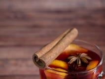 Το φλυτζάνι γυαλιού του κόκκινου κρασιού θέρμανε το κρασί σε ένα ξύλινο υπόβαθρο με τα καρυκεύματα και το πορτοκάλι κανέλας Εκλεκ Στοκ εικόνα με δικαίωμα ελεύθερης χρήσης