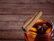 Το φλυτζάνι γυαλιού του κόκκινου κρασιού θέρμανε το κρασί σε ένα ξύλινο υπόβαθρο με τα καρυκεύματα και το πορτοκάλι κανέλας Εκλεκ Στοκ Εικόνες