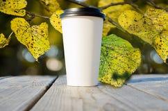 Το φλυτζάνι εγγράφου με τον καφέ στέκεται στο ξύλινο επιτραπέζιο πανδοχείο στο πάρκο φθινοπώρου Στοκ φωτογραφία με δικαίωμα ελεύθερης χρήσης