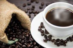 Το φλυτζάνι καφέ με τα φασόλια καπνού και καφέ στο σάκο στον ξύλινο πίνακα, ποτά και χαλαρώνει την έννοια, για τη διαφήμιση στοκ εικόνες