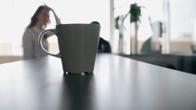 Το φλυτζάνι καφέ τίθεται στο μετρητή με τους κουβεντιάζοντας συναδέλφους στο υπόβαθρο απόθεμα βίντεο