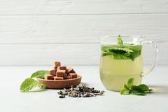 Το φλυτζάνι με το αρωματικό τσάι μεντών, ξεραίνει τα φύλλα και τους κύβους ζάχαρης στον πίνακα Στοκ Εικόνες