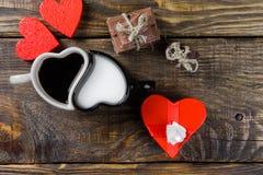 Το φλυτζάνι με μορφή των καρδιών, το ένα που χύθηκε τον καφέ στο άλλο γάλα, έπειτα ο τεμαχισμένος σπάγγος σοκολάτας έδεσε γύρω απ στοκ φωτογραφία με δικαίωμα ελεύθερης χρήσης
