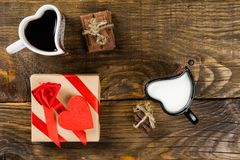 Το φλυτζάνι με μορφή των καρδιών, το ένα που χύθηκε τον καφέ στο άλλο γάλα, έπειτα ο τεμαχισμένος σπάγγος σοκολάτας έδεσε γύρω απ στοκ φωτογραφίες με δικαίωμα ελεύθερης χρήσης
