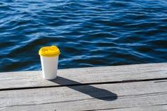 Το φλυτζάνι της Λευκής Βίβλου με ένα κίτρινο πλαστικό καπάκι στέκεται στους πίνακες στην ακτή της λίμνης στοκ εικόνες