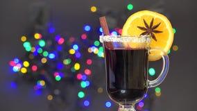 Το φλυτζάνι του θερμαμένου κρασιού με τη φέτα του πορτοκαλιού και της κανέλας, θολώνει τα ζωηρόχρωμα φω'τα στο υπόβαθρο, διάθεση  φιλμ μικρού μήκους