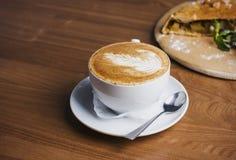 Το φλυτζάνι του cappuccino και strudel της Apple στο ξύλινο υπόβαθρο Στοκ Εικόνες