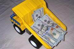το φορτηγό το φορτηγό απορρίψεων με τα χρήματα σε ένα κίτρινο χρώμα δολαρίων σωμάτων ο Μαύρος ροδών στοκ εικόνες
