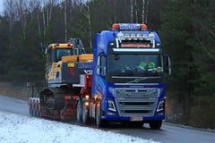 Το φορτηγό της VOLVO FH16 μεταφέρει τον εκσκαφέα αντιολισθητικών αλυσίδων Στοκ εικόνες με δικαίωμα ελεύθερης χρήσης