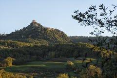 Το φρούριο Tentennano επάνω από τον οπωρώνα σε ένα μικρό χωριουδάκι στο d'Orcia Castiglione στοκ εικόνες