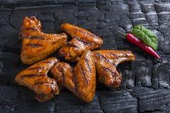 Το φτερό κοτόπουλου που ψήθηκε στη σχάρα τηγάνισε το μαύρο υπόβαθρο του ξυλάνθρακα σχάρα σχαρών που απομονώνε Στοκ εικόνα με δικαίωμα ελεύθερης χρήσης