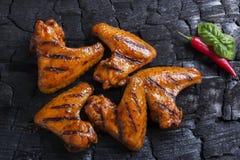 Το φτερό κοτόπουλου που ψήθηκε στη σχάρα τηγάνισε το μαύρο υπόβαθρο του ξυλάνθρακα σχάρα σχαρών που απομονώνε Στοκ Φωτογραφίες