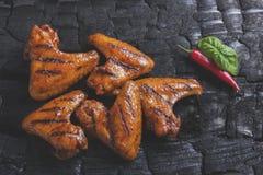 Το φτερό κοτόπουλου που ψήθηκε στη σχάρα τηγάνισε το μαύρο υπόβαθρο του ξυλάνθρακα σχάρα σχαρών που απομονώνε Στοκ Εικόνα