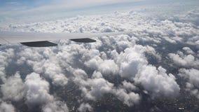 Το φτερό του αεροπλάνου πέρα από τα άσπρα χνουδωτά σύννεφα Η γη βλέπει κάτω από το φτερό των αεροσκαφών απόθεμα βίντεο