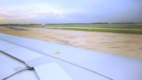 Το φτερό του αεροπλάνου επιβατών που κινείται στο διάδρομο ή το ταξί προετοιμάζεται για την απογείωση στον αερολιμένα φιλμ μικρού μήκους