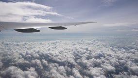 Το φτερό των κινήσεων αεροσκαφών πέρα από τον άσπρο σωρείτη καλύπτει Φως του ήλιου και σαφής μπλε ουρανός στον ορίζοντα φιλμ μικρού μήκους