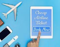Το φτηνό εισιτήριο αερογραμμών χτυπά το κουμπί στην ταμπλέτα στοκ εικόνες
