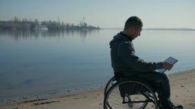 Το φυσικά με ειδικές ανάγκες άτομο κάθεται σε μια αναπηρική καρέκλα στην ακτή, στο lap-top χεριών απόθεμα βίντεο