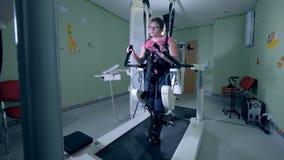 Το φυσικά προκλημένο νέο κορίτσι περνά από μια πρακτική περπατήματος με τη βοήθεια του εξοπλισμού αποκατάστασης απόθεμα βίντεο