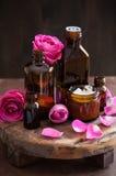 Το φυσικό καλλυντικό στα βάζα γυαλιού και αυξήθηκε aromatherapy SPA λουλουδιών Στοκ φωτογραφία με δικαίωμα ελεύθερης χρήσης