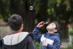Το φυσώντας σαπούνι παιδιών βράζει υπαίθρια Στοκ Εικόνα