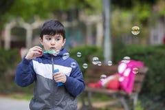 Το φυσώντας σαπούνι παιδιών βράζει υπαίθρια Στοκ Φωτογραφία