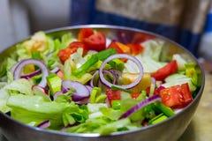 Το φυτικό κρεμμύδι σαλάτας χτυπά τις juicy ντομάτες σε ένα κύπελλο μετάλλων Στοκ Εικόνα