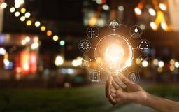 Το φως εκμετάλλευσης χεριών bulbl παρουσιάζει παγκόσμια ` s κατανάλωση στοκ φωτογραφίες