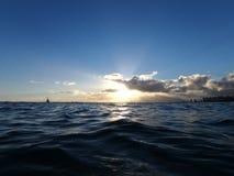 Το φως ηλιοβασιλέματος λάμπει μέσω των σύννεφων όπως τα κύματα κυματίζουν στο ο Στοκ Φωτογραφία