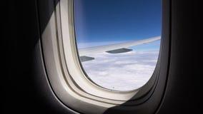 Το φως του ήλιου λάμπει μέσω του παραθύρου του αεροπλάνου Άποψη του ουρανού από το κάθισμα επιβατών απόθεμα βίντεο