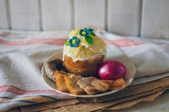 Το φωτεινό κόκκινο αυγό Πάσχας, το μπέϊκον, το λουκάνικο και Πάσχα πασπαλίζουν με ψίχουλα στο άσπρο πιάτο σε καφετί χαρτί πετσετώ στοκ φωτογραφίες