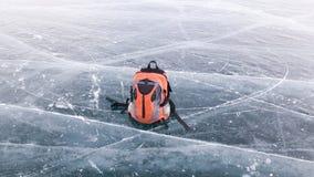 Το φωτεινό μικρό σακίδιο πλάτης πεζοπορίας βρίσκεται στον πάγο της παγωμένης λίμνης Baikal στη Σιβηρία Το ταξίδι-πεζοπορώ στην πα στοκ φωτογραφία